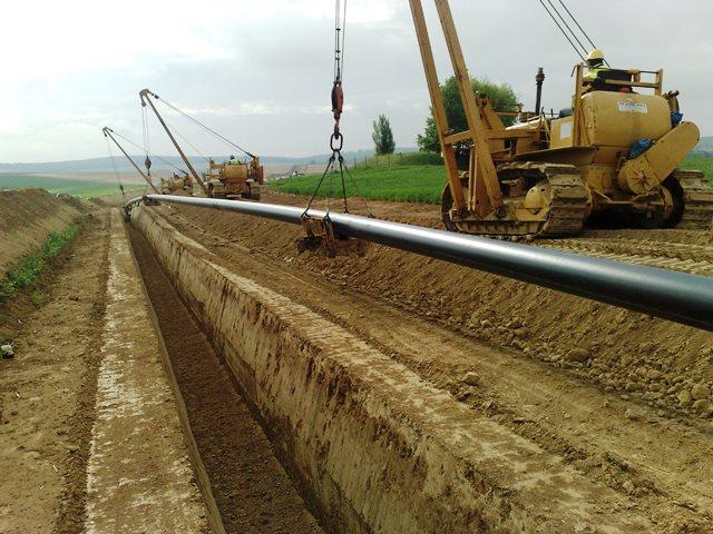 Pipeline-Rohre beim Absenken in den Graben.