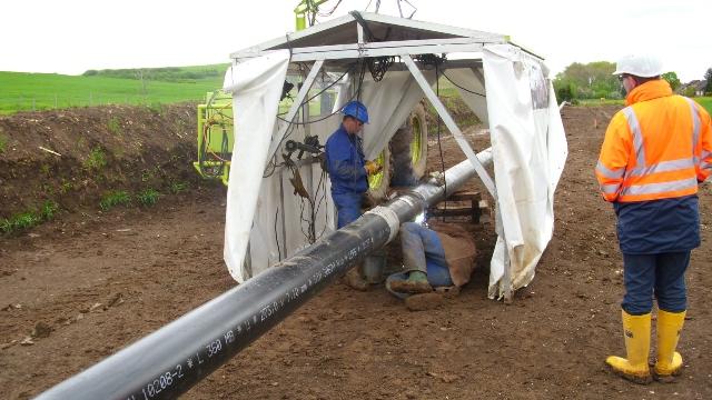 Arbeiter schweißen die Rohre zusammen.
